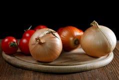 Tomates napiformes de las cebollas en una tabla vieja Fotos de archivo libres de regalías