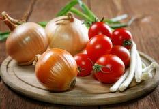 Tomates napiformes de las cebollas en una tabla vieja Fotografía de archivo libre de regalías