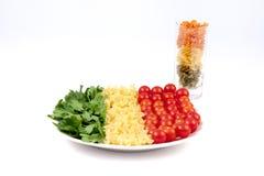 Tomates, pastas e hierba Imagenes de archivo