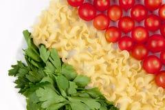 Tomates, pastas e hierba Fotos de archivo