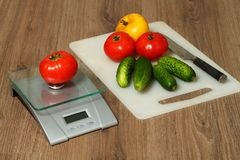 Tomates, pepinos e faca em uma placa de corte Fotos de Stock Royalty Free