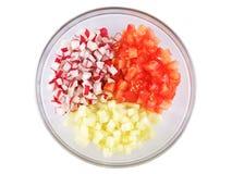 Tomates, pepinos e rabanetes, corte em cubos em uma bacia de vidro, em um fundo branco Fotos de Stock