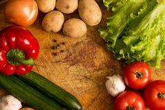 Tomates, pepinos, verdes, ajo, patatas, pimienta en una tabla de cortar con un lugar para los primers de registración Imagen de archivo
