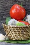 Tomates, pepinos y ajo en una cesta Fotos de archivo