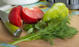 Tomates, pimentas, manjericão, aneto e uma faca em um cu Foto de Stock