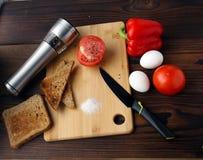 Tomates, pimientas y huevos en la tabla imagen de archivo