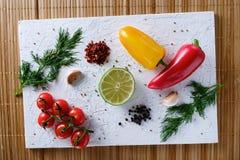 Tomates, poivrons, ail, chaux et aneth Photographie stock libre de droits