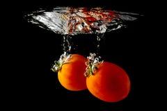 Tomates que caem através da água Imagens de Stock Royalty Free