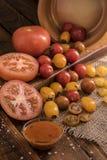 Tomates que espalham para fora em uma placa de madeira Fotografia de Stock