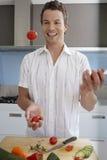 Tomates que hacen juegos malabares del hombre mientras que prepara la comida en cocina Imágenes de archivo libres de regalías