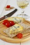 Tomates, queso verde en el biscote curruscante y vidrio de vino blanco Imágenes de archivo libres de regalías