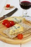 Tomates, queso verde en el biscote curruscante y vidrio de vino rojo Imagen de archivo libre de regalías