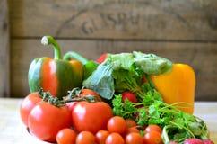 Tomates, rábanos, pimientas y perejil en la tajadera de madera Imágenes de archivo libres de regalías