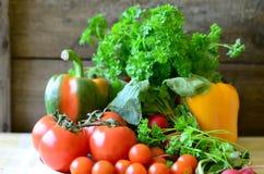 Tomates, rábanos, pimientas y perejil en la tajadera de madera Imagen de archivo