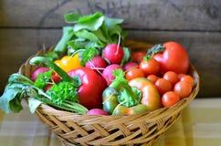 Tomates, rábanos, pimientas y perejil en la tajadera de madera Imagenes de archivo