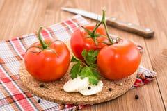 Tomates, rebanadas de queso y perejil en un substrato en una tabla de madera Fotografía de archivo