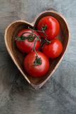 Tomates red delicious fraîches dans le plat de coeur-forme Image stock