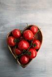 Tomates red delicious fraîches dans le plat de coeur-forme Photographie stock libre de droits