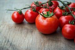 Tomates red delicious fraîches sur un vieux backgro de table en bois Image stock