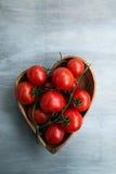 Tomates red delicious frescos en placa de la corazón-forma Imagenes de archivo