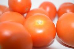 Tomates rojos brillantes con el fondo blanco nada  Imagenes de archivo