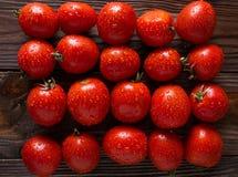 Tomates rojos con descensos del agua Tomates de diversas variedades Fondo de los tomates Foto de archivo