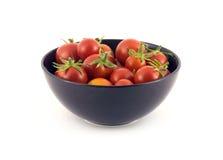 Tomates rojos en el cuenco violeta aislado en blanco Fotos de archivo