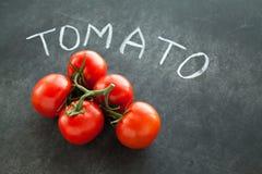 Tomates rojos en rama verde Foto de archivo libre de regalías