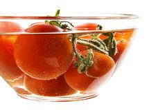 Tomates rojos en una placa con agua Fotografía de archivo