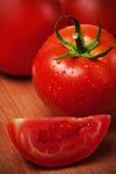 Tomates rojos en una tarjeta de corte Imagenes de archivo