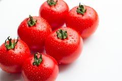 Tomates rojos frescos con descensos en un fondo blanco Imagen de archivo