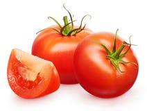 Tomates rojos frescos con las hojas y la rebanada verdes Foto de archivo
