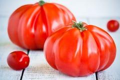 Tomates rojos frescos de la herencia en un fondo de madera Fotografía de archivo libre de regalías