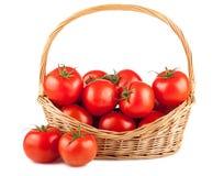 Tomates rojos frescos en cesta de mimbre Imagenes de archivo