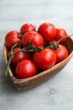 Tomates rojos frescos en placa de madera Imágenes de archivo libres de regalías