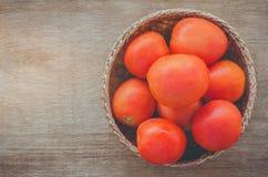 Tomates rojos frescos en una cesta marrón Imagen de archivo