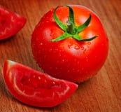 Tomates rojos frescos en una tarjeta de corte Fotografía de archivo