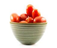 Tomates rojos, largos en una taza verde en un fondo blanco Fotos de archivo