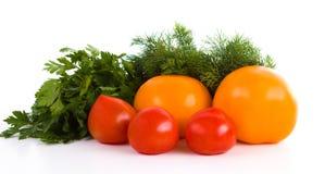 Tomates rojos y amarillos con el eneldo y el perejil aislados en blanco imagenes de archivo