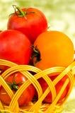 Tomates rojos y amarillos en una cesta de mimbre Fotos de archivo libres de regalías