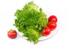 Tomates rojos y lechuga verde en el fondo blanco Fotos de archivo libres de regalías