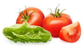 Tomates rouges avec les feuilles, la tranche et la salade vertes sur le blanc Photographie stock libre de droits