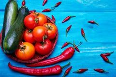 Tomates rouges avec les poivrons de piment et la courgette verte sur un fond en bois Ingrédients de sauce à ketchup légumes Photographie stock libre de droits