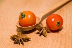 Tomates rouges dans des anis de cuillère et d'étoile sur une surface en bois Photographie stock