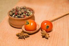 Tomates rouges en anis de cuillère, de poivre et d'étoile Images stock