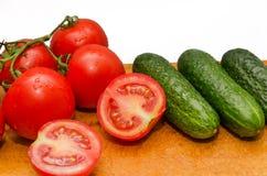 Tomates rouges et concombre vert à bord Image libre de droits