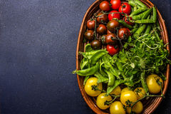 Tomates rouges et jaunes, salade de cresson et pois sur l'essai Récolte ou concept sain propre de consommation Vue supérieure Photo stock