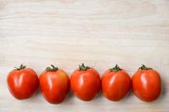 Tomates rouges fraîches sur le fond en bois de table Images stock