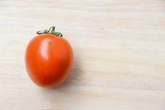 Tomates rouges fraîches sur le fond en bois lumineux de table Photos libres de droits