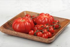 Tomates rouges juteuses mûres dans un plat en bois Photo libre de droits